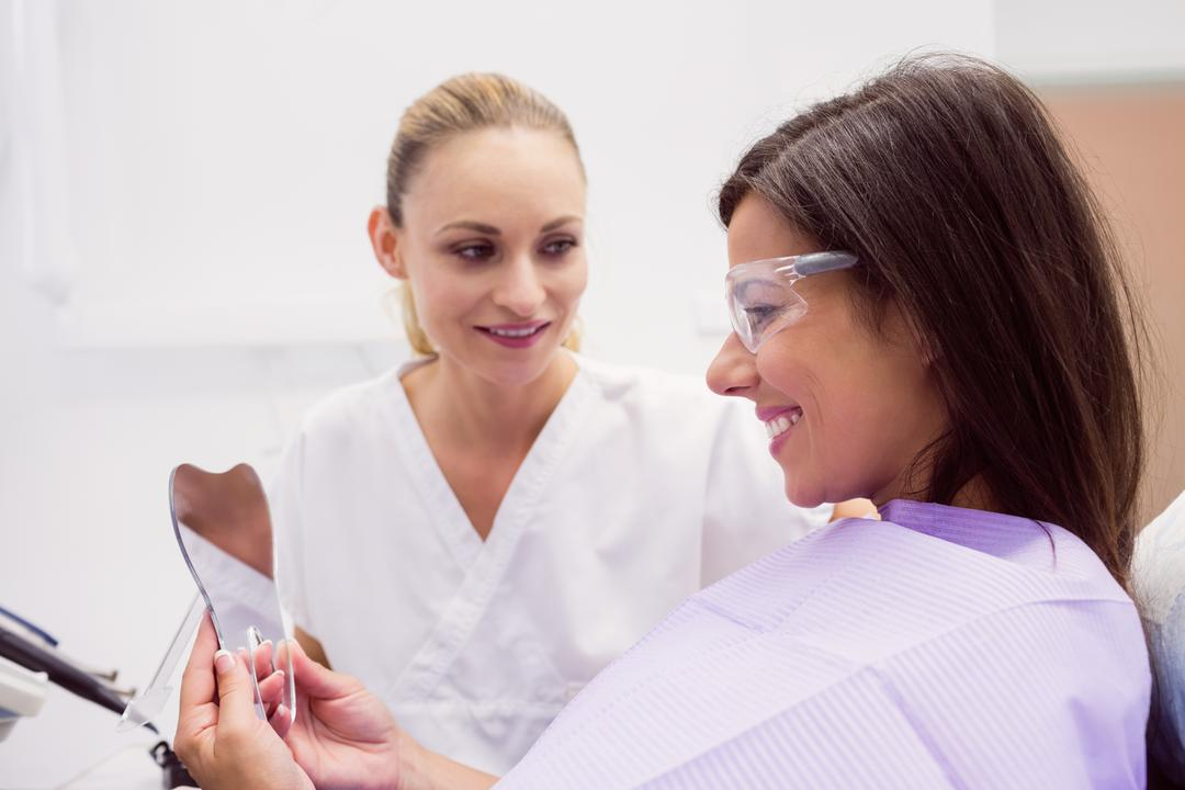 Female patient smiling while looking on the mirror