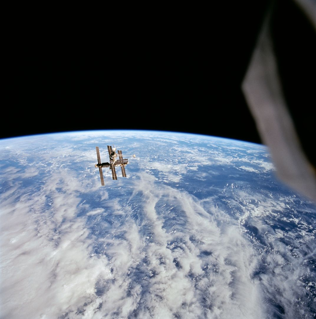 STS063-708-095 (6 Feb 1995) --- Cumulus and other clouds over the ocean form the backdrop for this scene of Russia's Mir space station during rendezvous operations by the Space Shuttle Discovery and Mir.  This photograph was taken as the Discovery was firing its Reaction Control Subsystem (RCS) thrusters to separate from Mir's proximity.  Onboard the Discovery were astronauts James D. Wetherbee, mission commander; Eileen M. Collins, pilot; Bernard A. Harris Jr., payload commander; mission specialists Janice Voss and C. Michael Foale; along with Russian cosmonaut Vladimir G. Titov.        EDITOR'S NOTE: This 70mm handheld Hasselblad frame has been cropped to enlarge Mir.