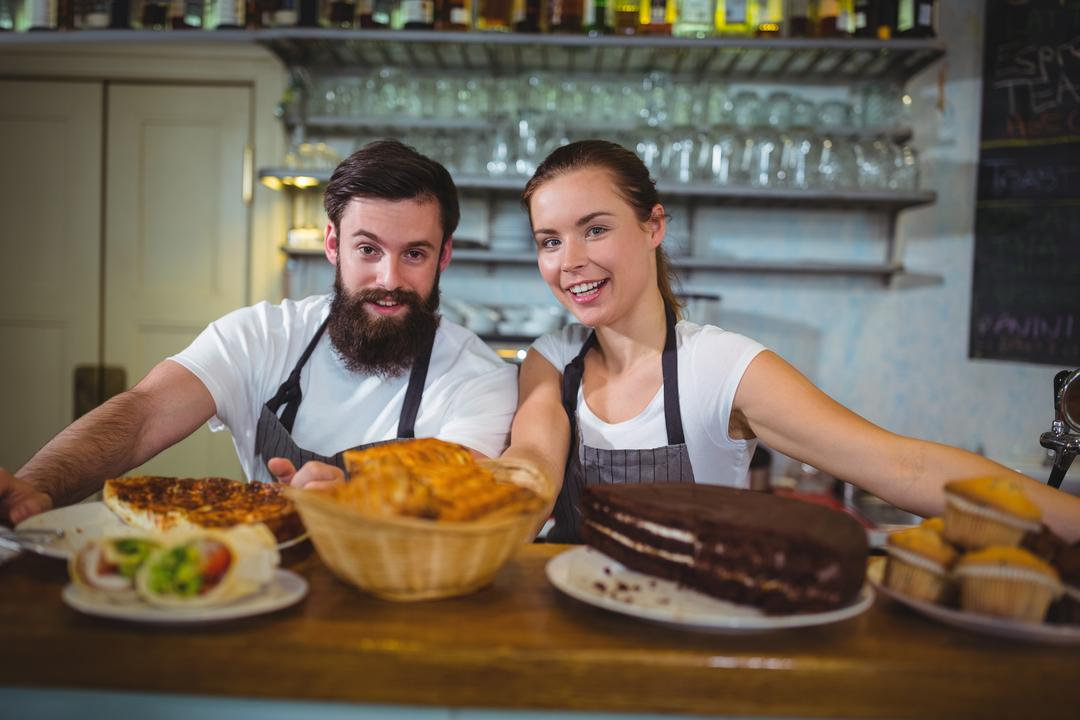 Portrait of waiter and waitress standing at counter in café