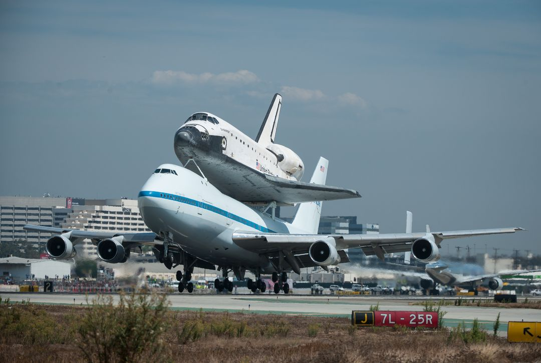 Space shuttle Endeavour, mounted atop a NASA 747 Shuttle Carrier Aircraft (SCA) lands at Los Angeles International Airport, Friday, Sept. 21, 2012. Endeavour, built as a replacement for space shuttle Challenger, completed 25 missions, spent 299 days in orbit, and orbited Earth 4,671 times while traveling 122,883,151 miles. Beginning Oct. 30, the shuttle will be on display in the California Science center's Samuel Oschin Space Shuttle Endeavour  Display Pavilion, embarking on its new mission to commemorate past achievements in space and educate and inspire future generations of explorers.Photo Credit: (NASA/Bill Ingalls)