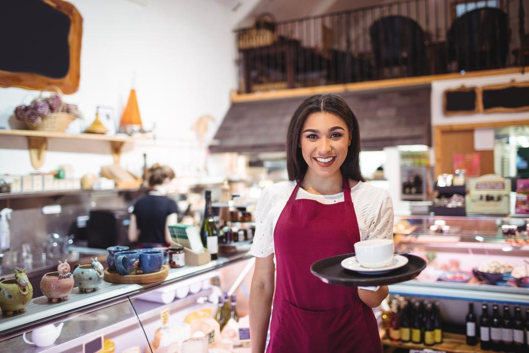 Portrait of smiling waitress serving a cup of coffee at counter in supermarket