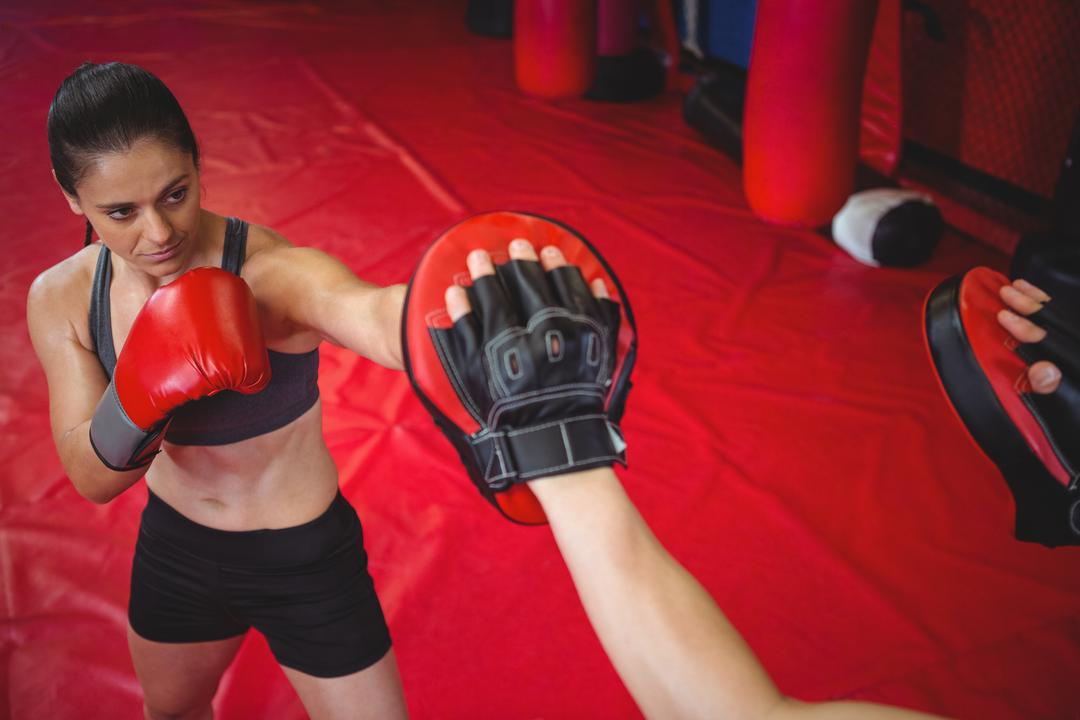 Female boxer practicing with trainer at fitness studio