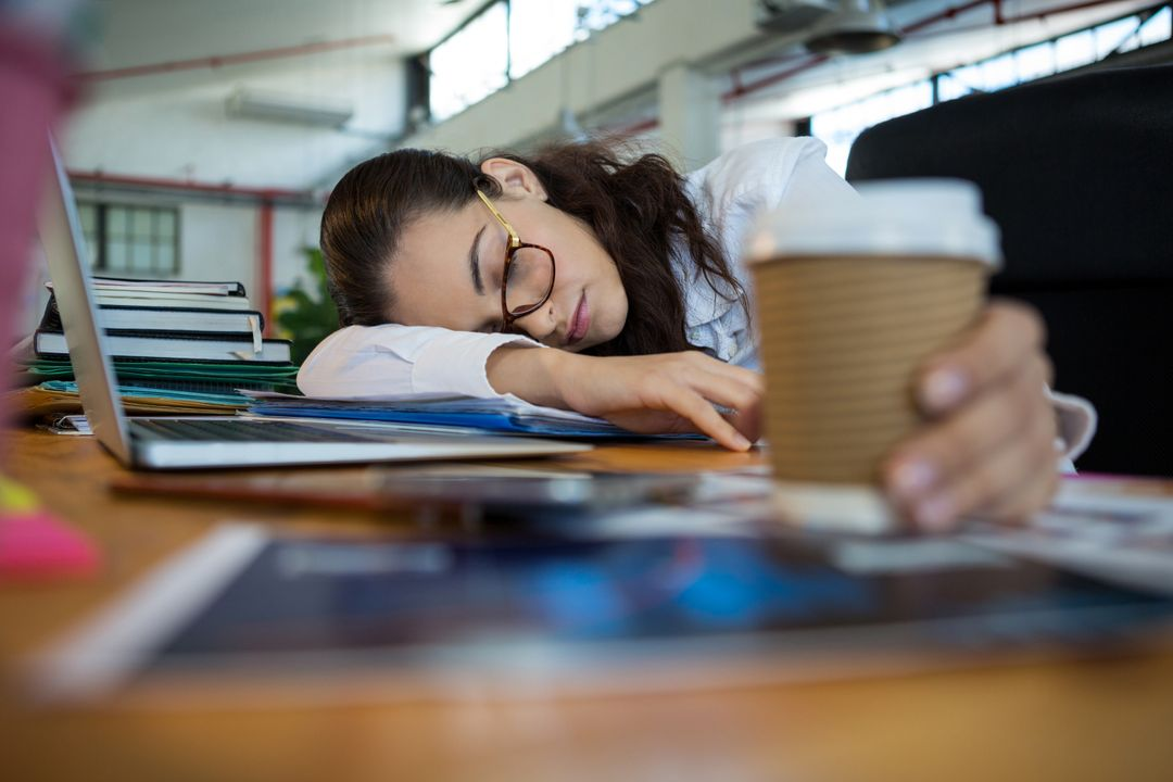 Tired female graphic designer holding disposable cup while sleeping on desk in office Free Stock Images from PikWizard
