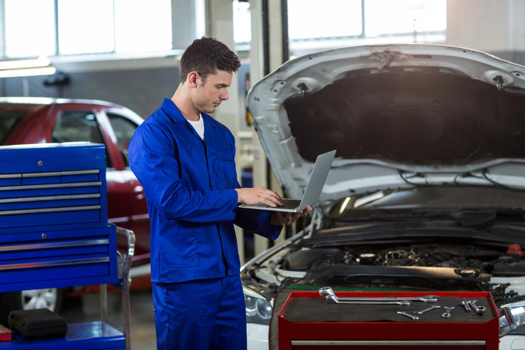 Mechanic using laptop in repair garage