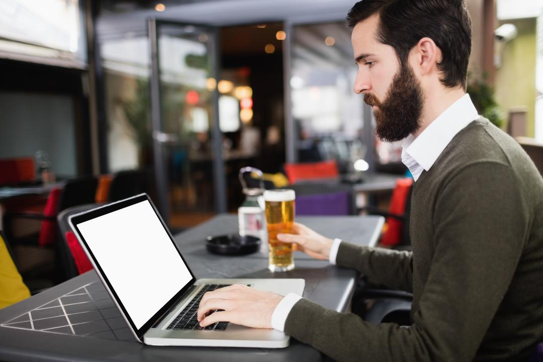 Man using laptop while having glass of beer in bar