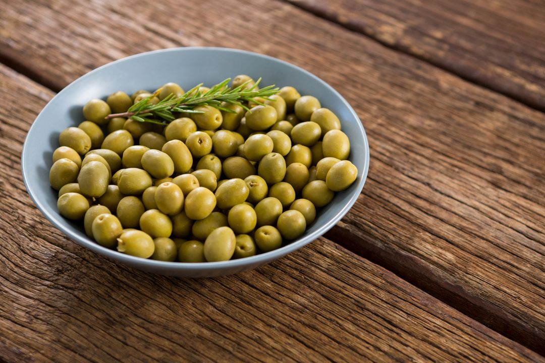 Garnished marinated olives in bowl on wooden table Free Stock Images from PikWizard