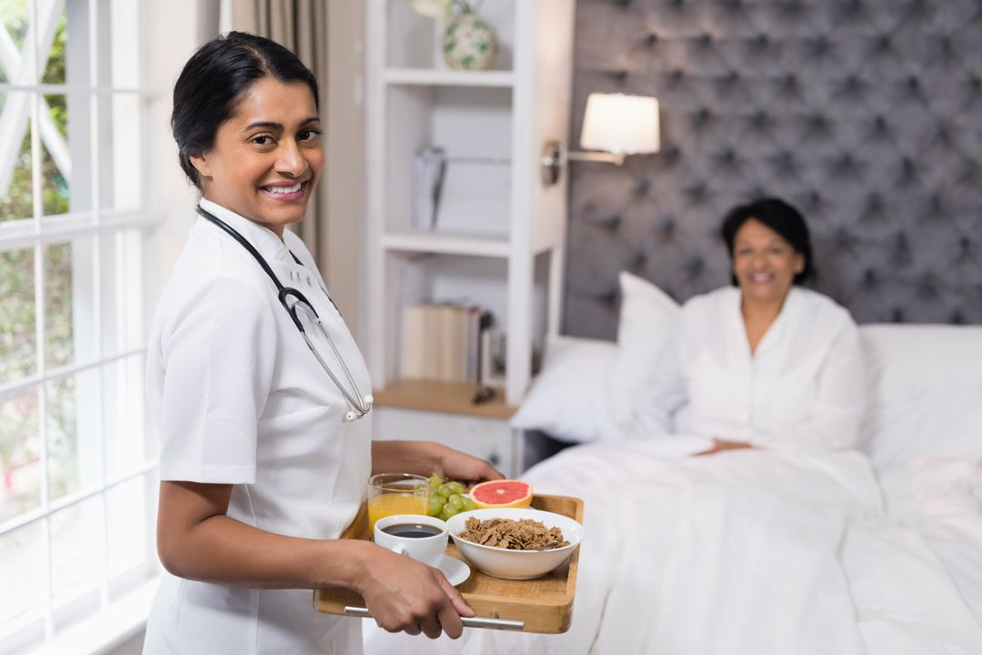 Portrait of nurse serving breakfast to patient resting on bed at home