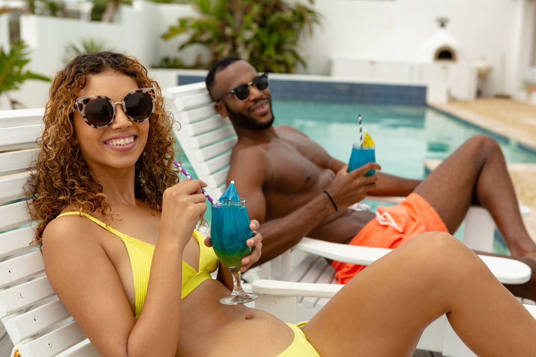 Side view of happy diverse couple having cocktail drink while relaxing on a sun lounger near swimming pool. Summer fun at home by the swimming pool