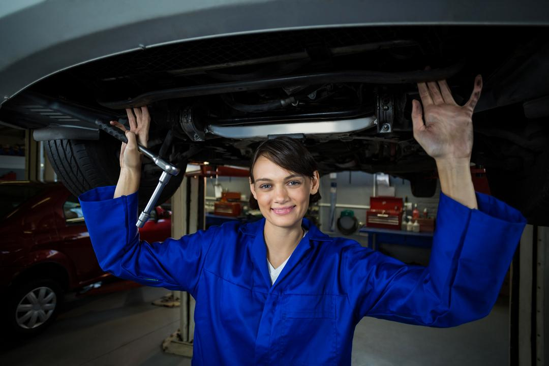 Female mechanic servicing a car in repair garage