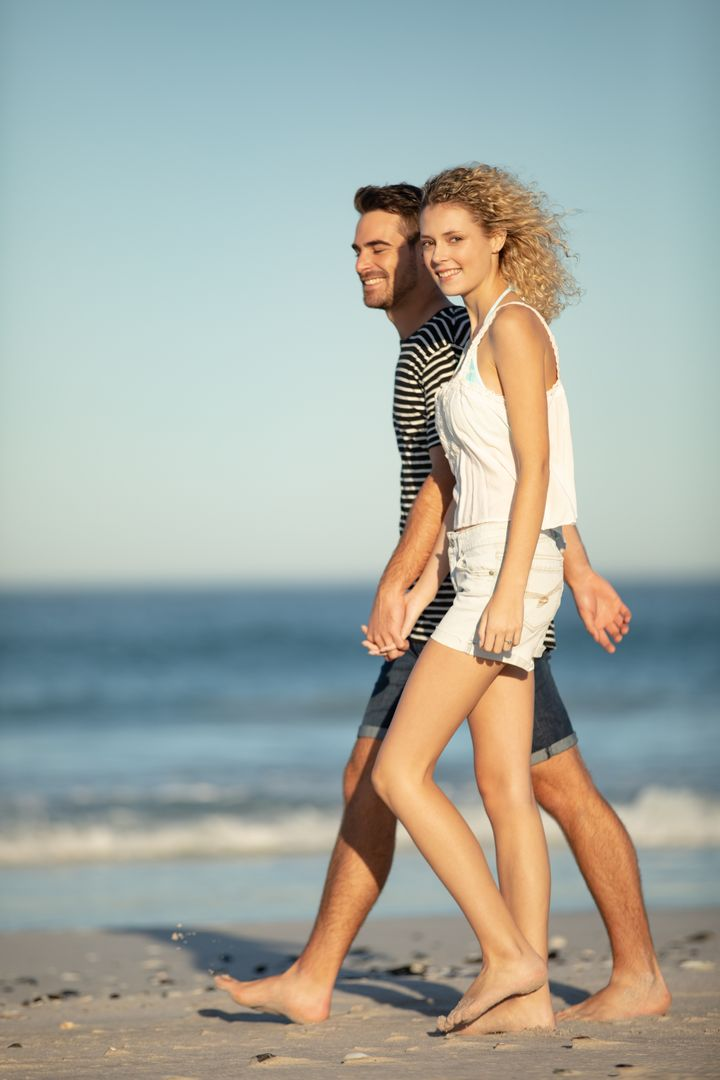 Happy Couple walking together hand in hand on the beach