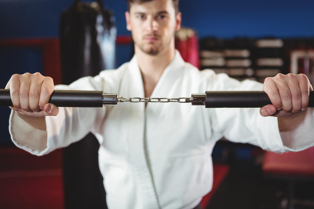 Karate player practicing with nunchaku in fitness studio Free Stock Images from PikWizard
