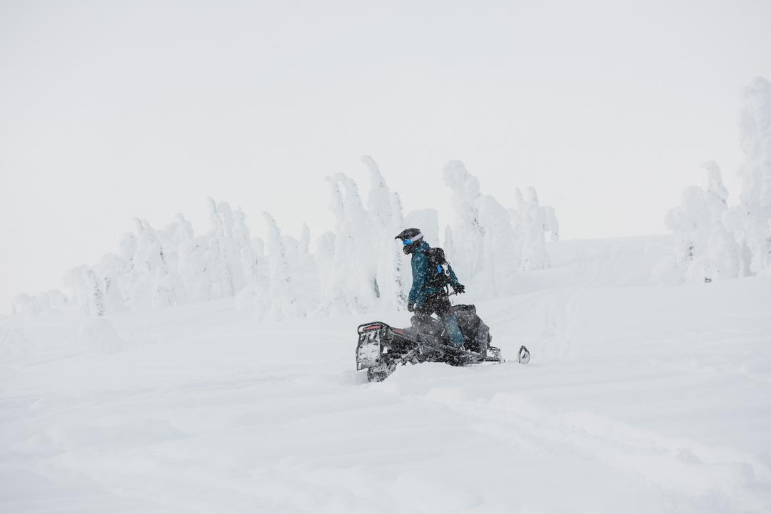 Man riding snowmobile in snowy alps during winter