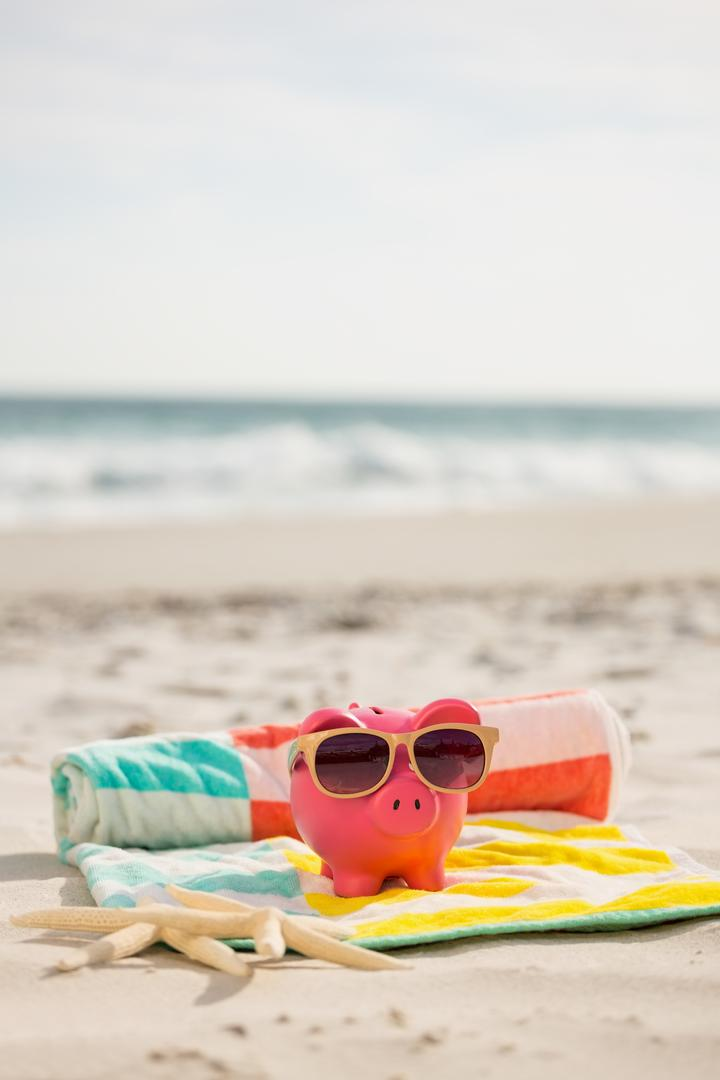 Two starfish and piggy bank with sunglasses on beach blanket at sand beach Free Stock Images from PikWizard