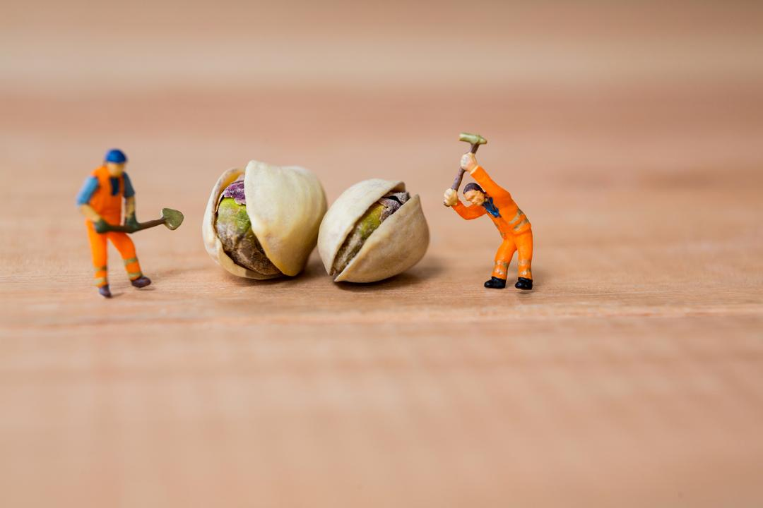 Conceptual image of miniature construction workers with pistachio nuts Free Stock Images from PikWizard