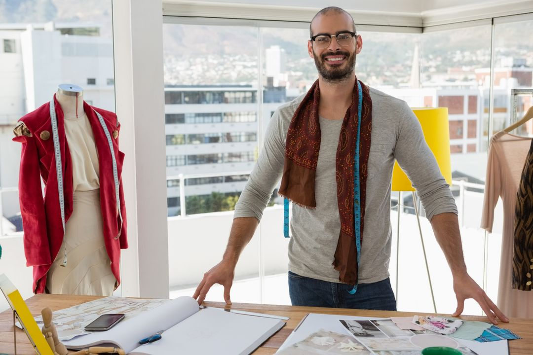 Portrait of fashion designer standing at table in studio Free Stock Images from PikWizard