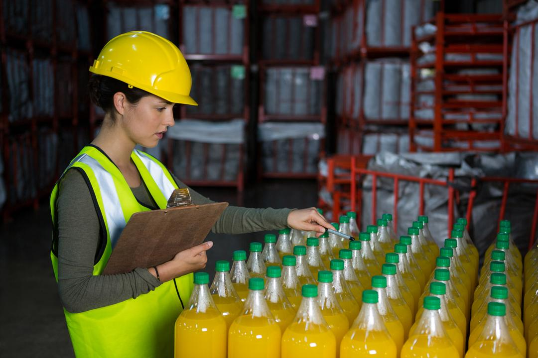 Female worker examining juice bottles in factory