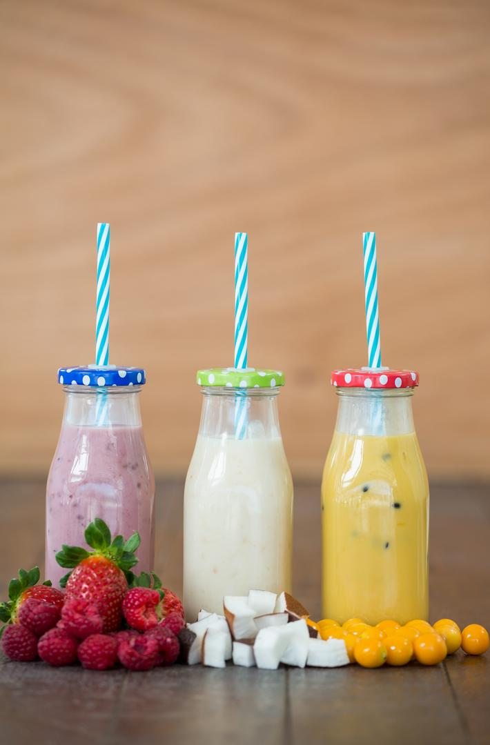 Three bottles with smoothies and fresh chopped fruits on wooden board Free Stock Images from PikWizard