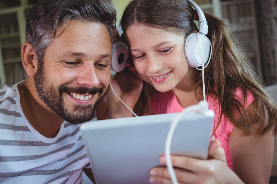 Father and daughter listening music on digital tablet at home Free Stock Images from PikWizard