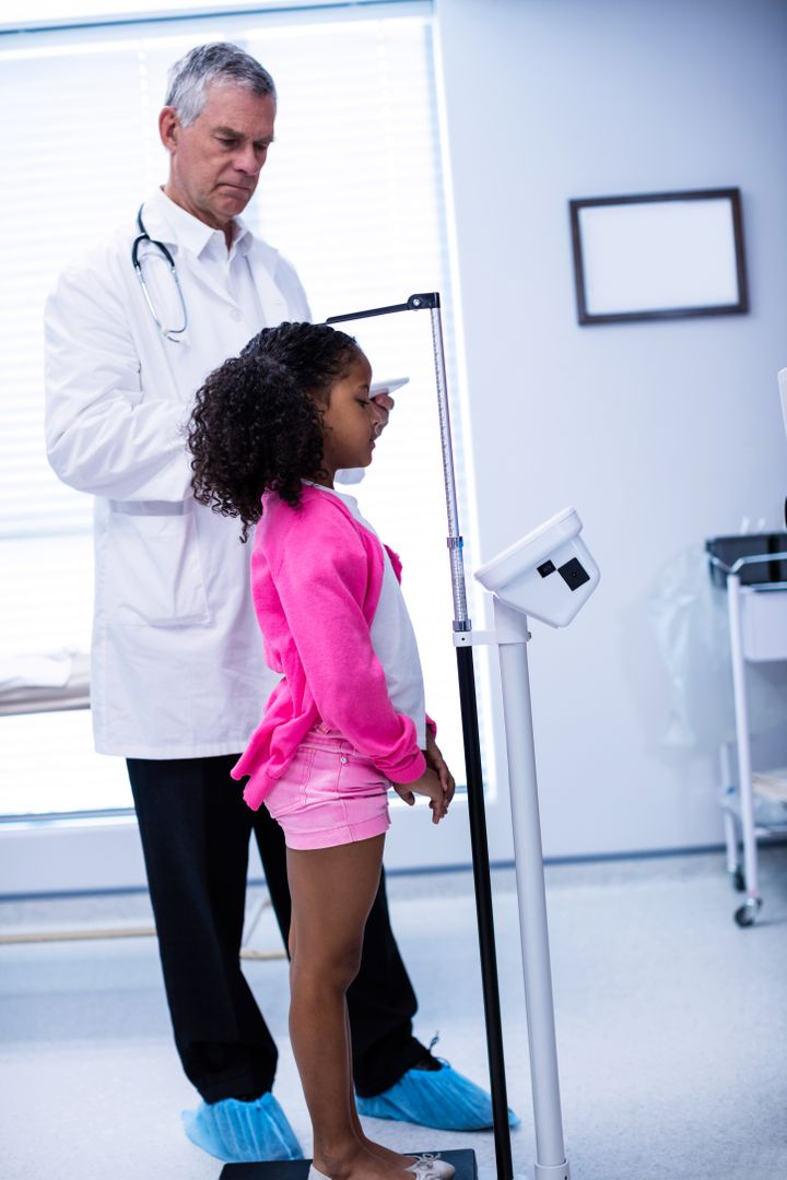Doctor measuring height of girl in clinic Free Stock Images from PikWizard