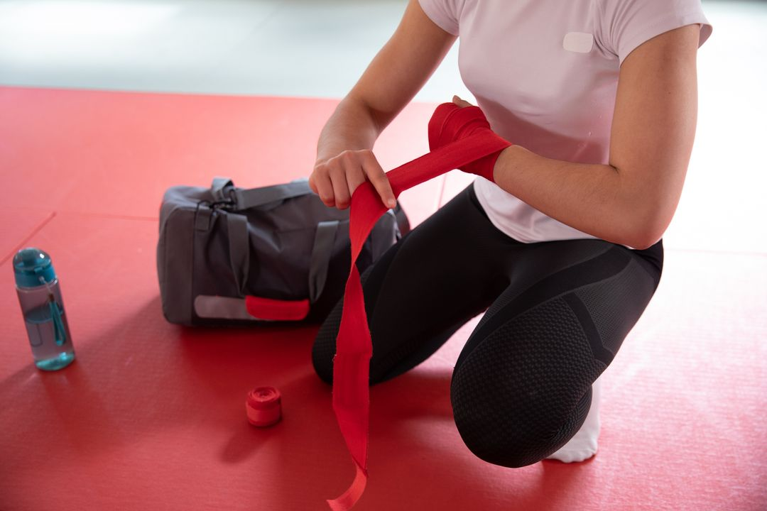 Low angle view of a Caucasian female judoka preparing for judo training, kneeling on a mat and wrapping her wrist with a red tape. Free Stock Images from PikWizard