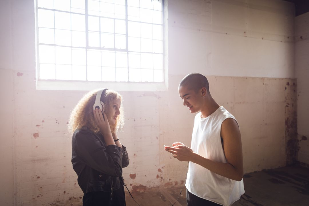 Side view of a hip young mixed race man and a hip young Caucasian woman in an empty warehouse, standing holding a smartphone and listening to music with headphones on. Free Stock Images from PikWizard