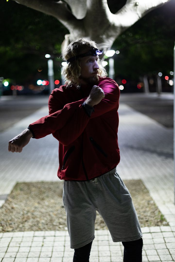 Front view of a fit Caucasian man with long blonde hair wearing sportswear exercising outdoors in the city the eveninig, standing and stretchering his arms, wearing head light. Free Stock Images from PikWizard