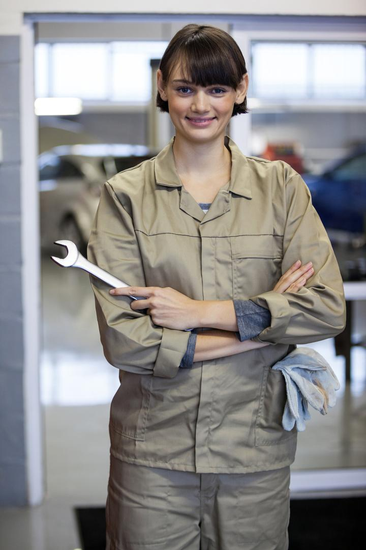 Portrait of female mechanic with arms crossed and spanner at the repair garage Free Stock Images from PikWizard