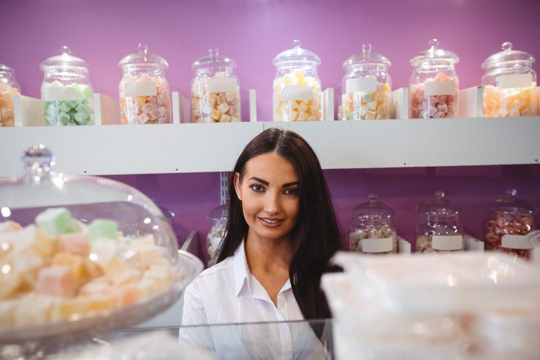 Portrait of female shopkeeper standing at turkish sweets counter in shop Free Stock Images from PikWizard