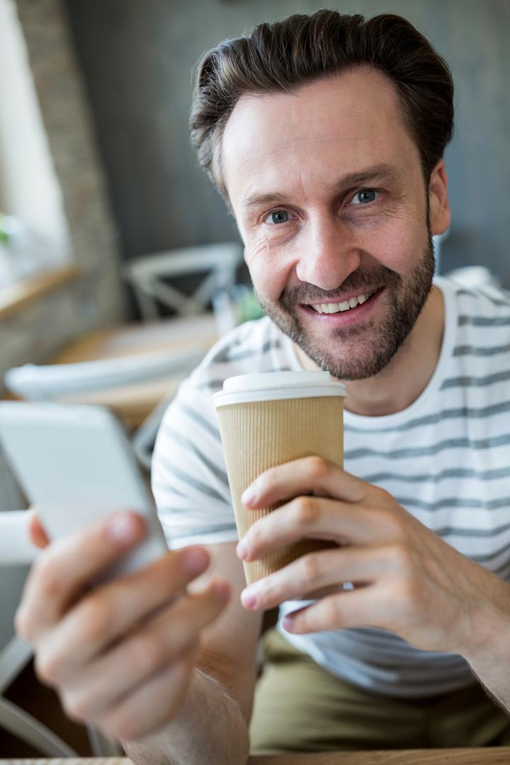 Portrait of smiling man holding mobile phone and disposable coffee cup in coffee shop