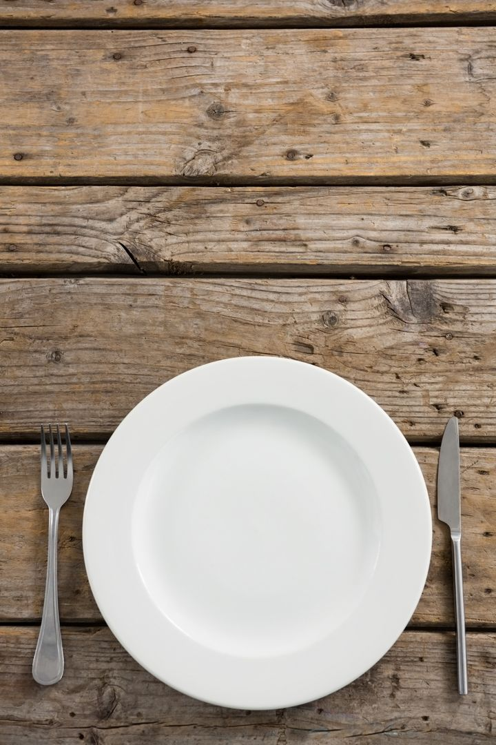 Overhead view of empty plate amidst fork and table knife on wooden table