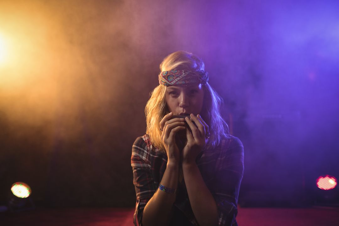 Portrait of confident female musician playing harmonica in illuminated nightclub Free Stock Images from PikWizard