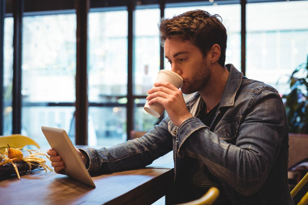 Man using digital tablet while having coffee in café