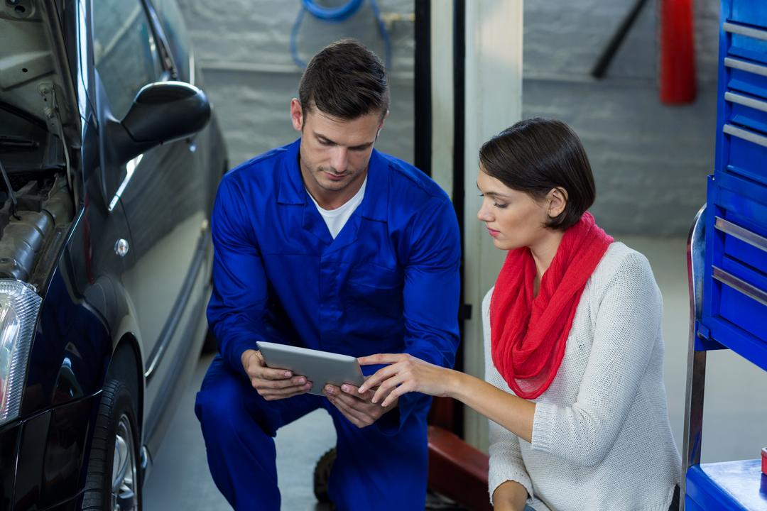 Mechanic using digital tablet with customer in repair garage