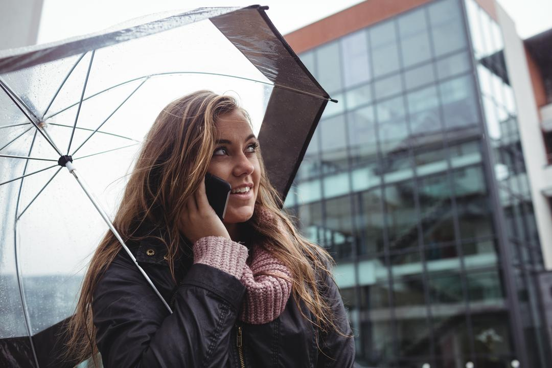 Beautiful woman holding an umbrella and talking on mobile phone at street Free Stock Images from PikWizard