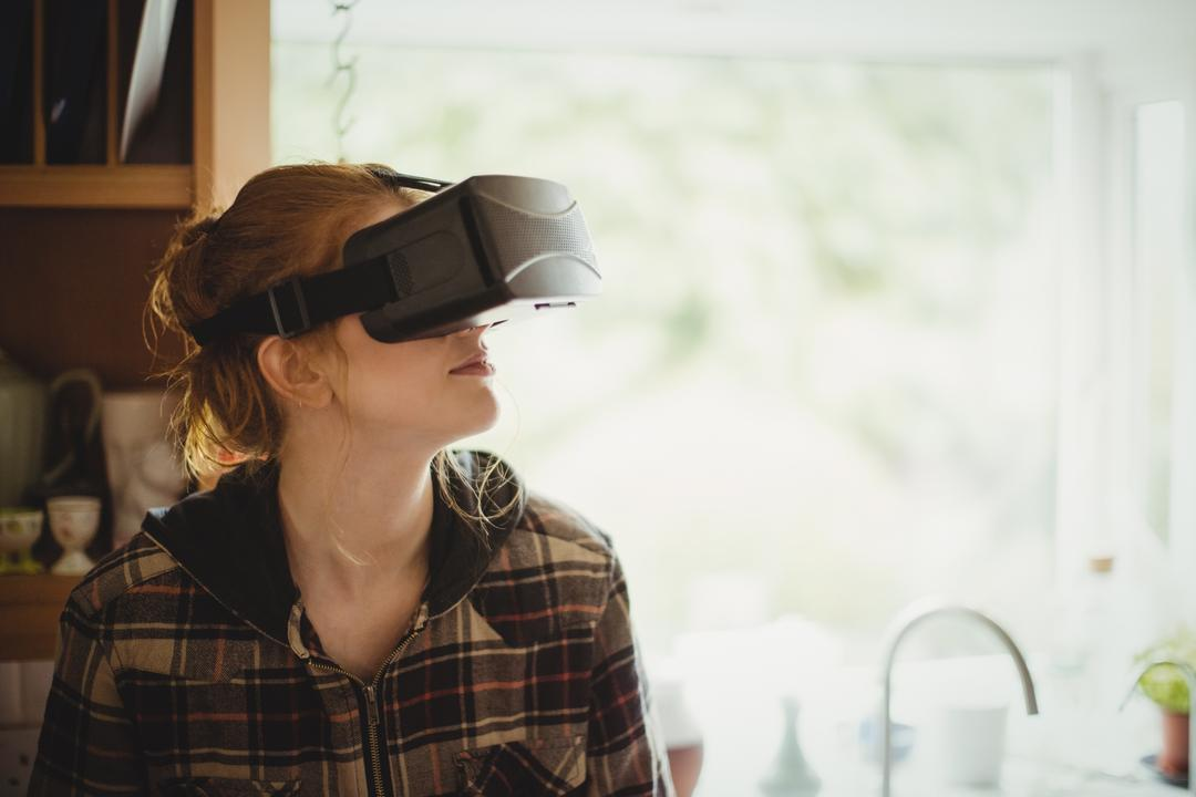 Woman experiencing virtual reality headset in kitchen at home