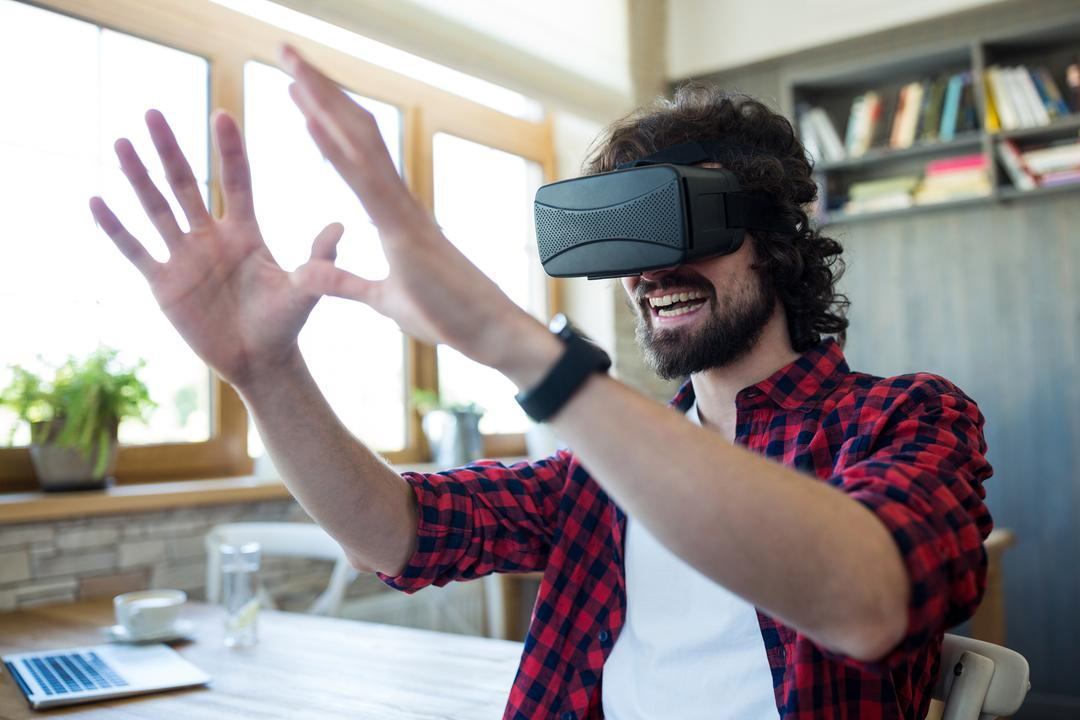 Happy man using virtual reality headset in coffee shop