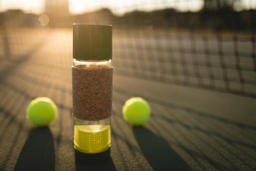 Close-up of tennis ball and water bottle in ground on a sunny day