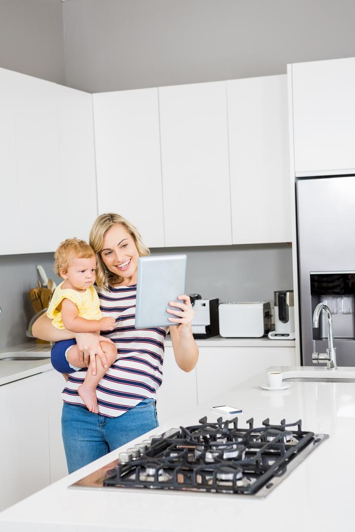 Mother and baby girl using digital tablet in kitchen at home Free Stock Images from PikWizard