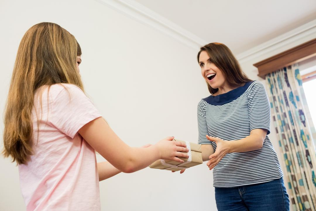 Mother receiving present from her daughter in living room at home