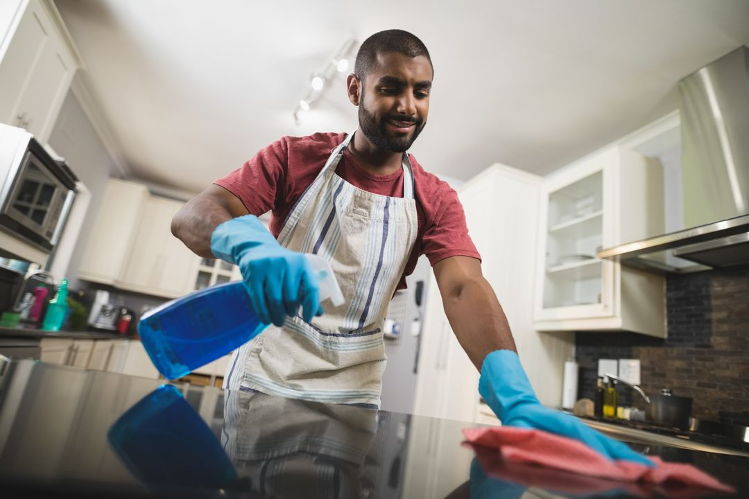 Low angle view of young man cleaning marble counter in kitchen at home