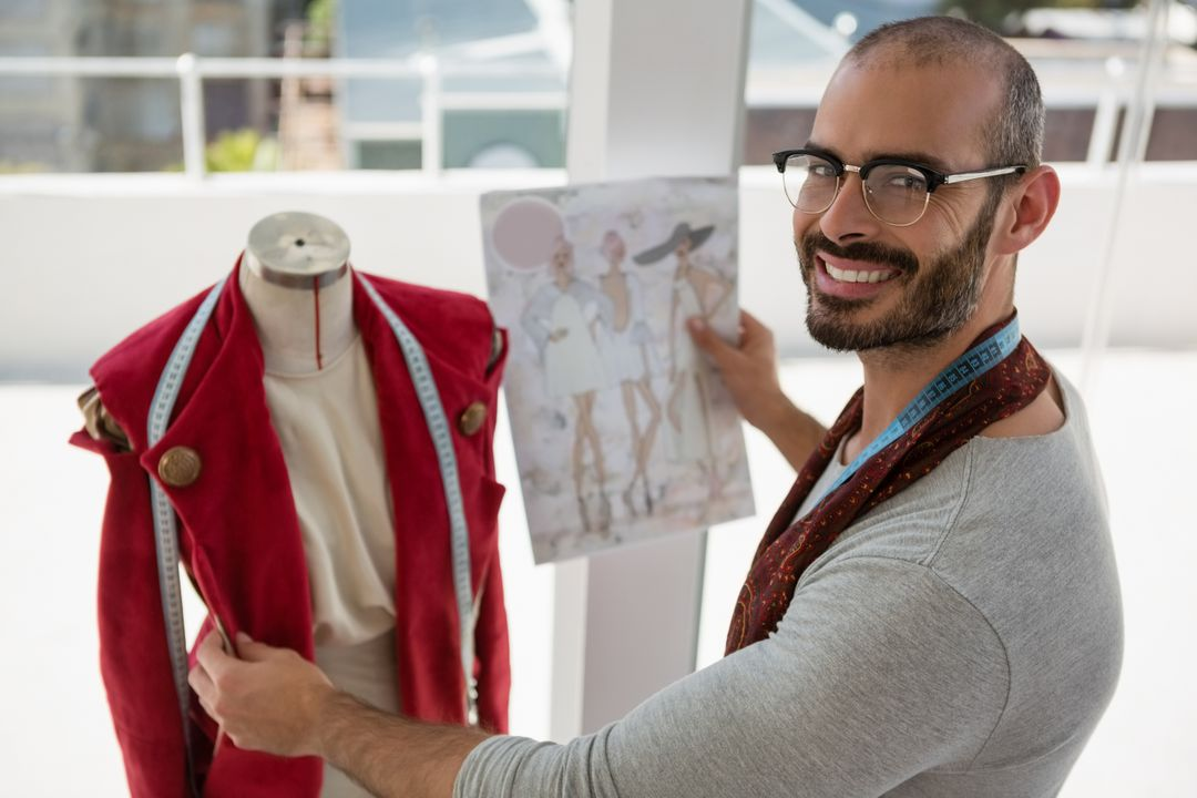 Portrait of smiling designer standing by mannequin at office Free Stock Images from PikWizard