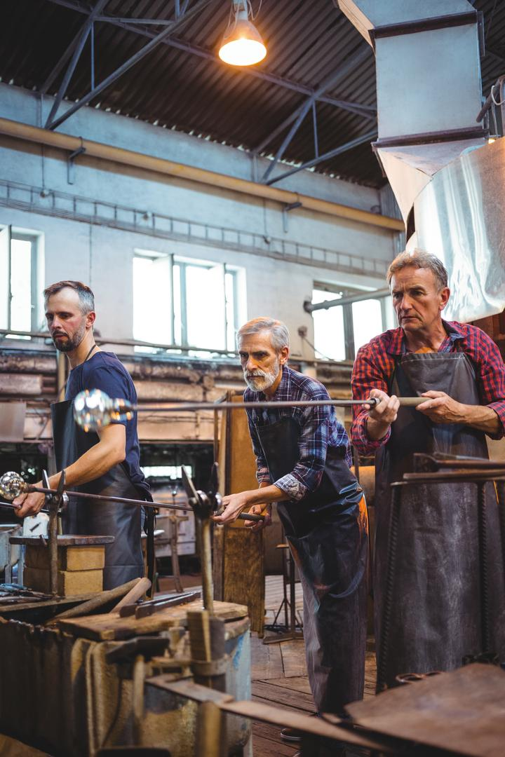Team of glassblower shaping a glass on the blowpipe at glassblowing factory Free Stock Images from PikWizard