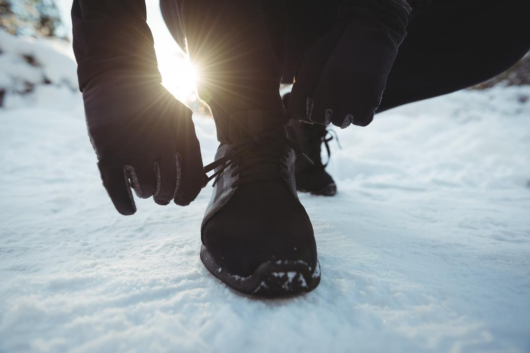 Close-up of man tying shoelaces in forest during winter
