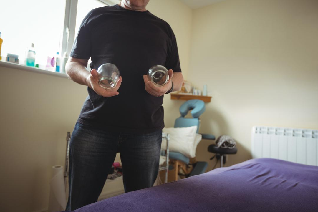 Therapist holding cupping glass in spa
