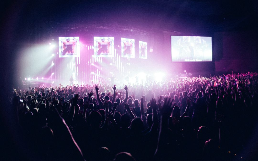 large crowd at concert with strobe lighting on stage background