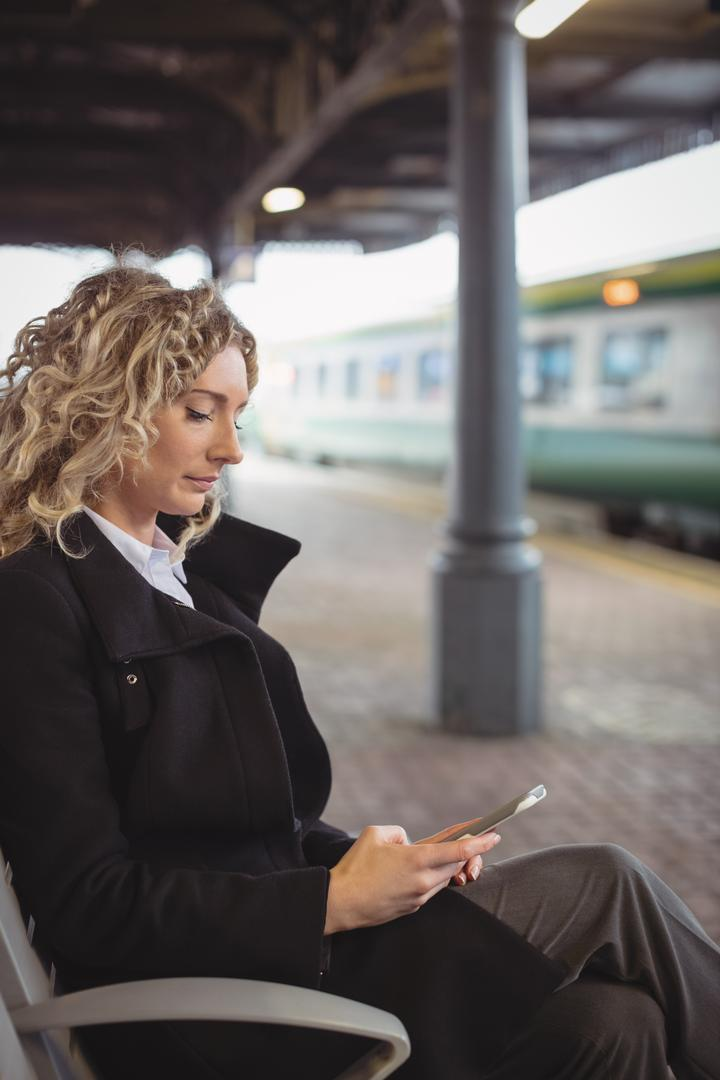 Woman sitting on platform using mobile phone at railway station