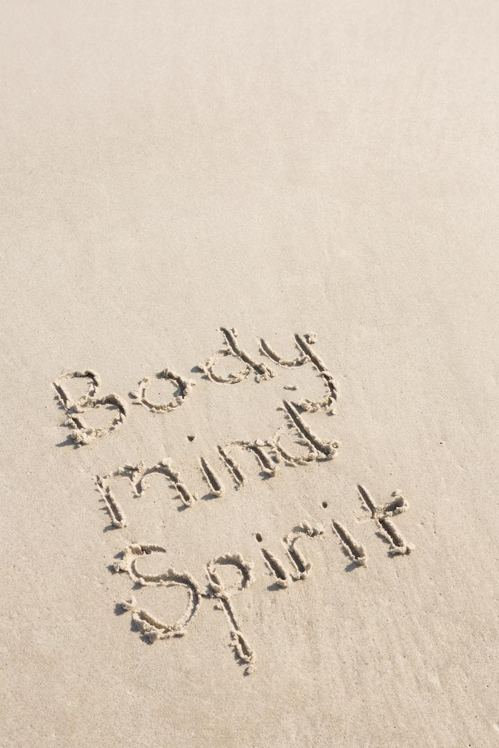 Body mind spirit written on sand at beach