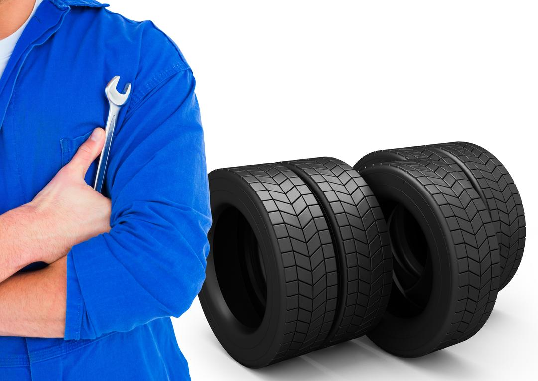 Mid section of mechanic holding a wrench against tires on white background