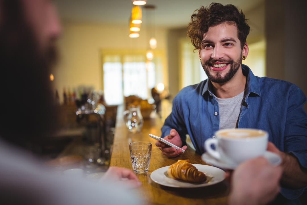 Waiter serving a cup of coffee to customer in café