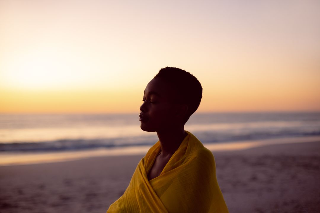 Young woman with eyes closed wrapped in yellow scarf on the beach